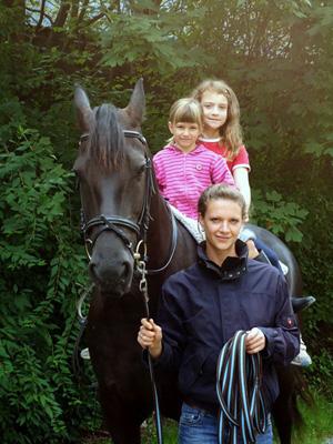 Johanna Kofler führt ein Pferd mit Kindern im Sattel